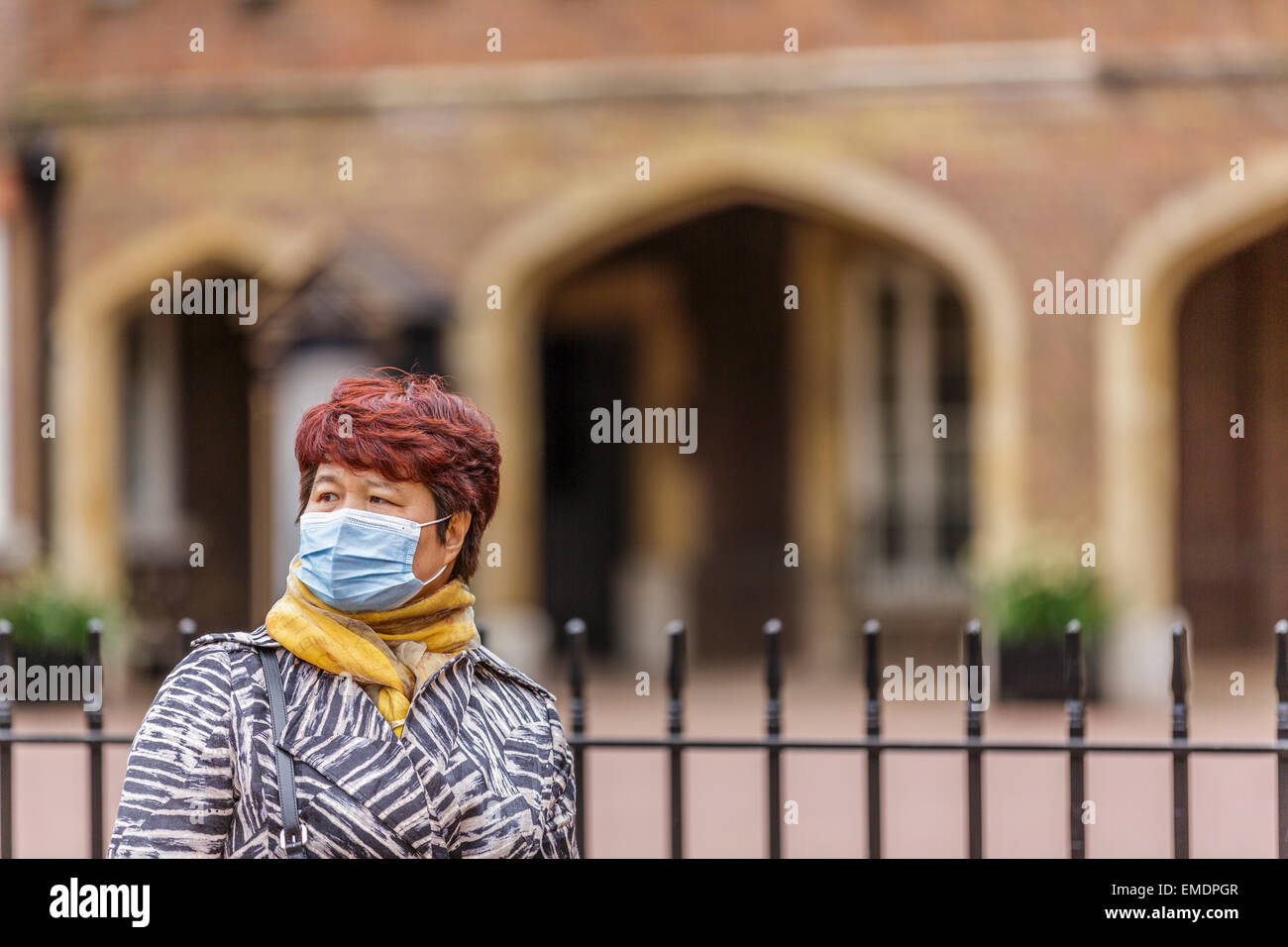 A female Oriental tourist with a surgical face mask standing outside St James's Palace London England UK - Stock Image