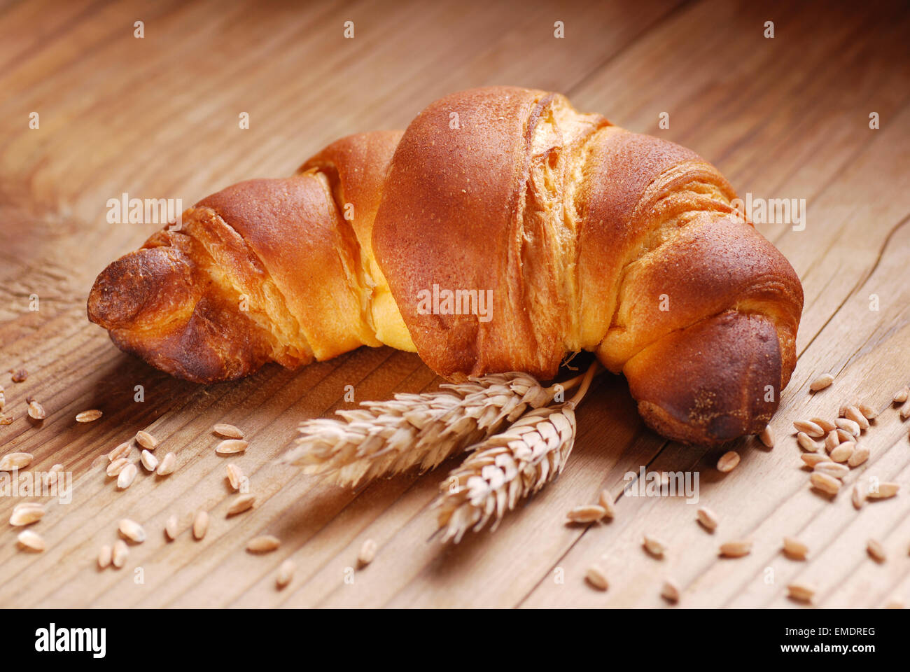warm croissant with ears of corn on the wooden table - Stock Image