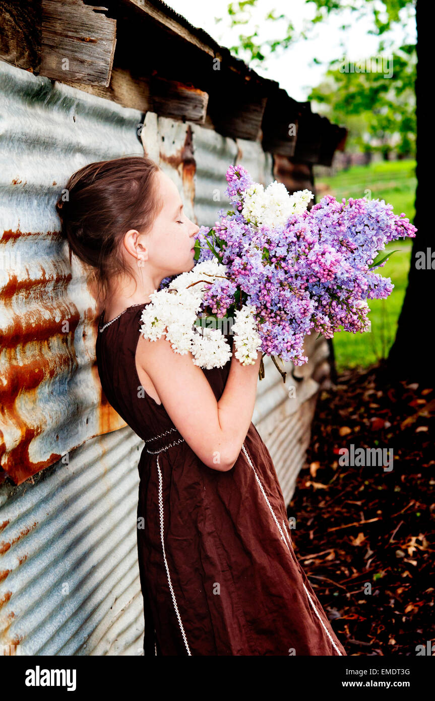 Girl smelling bouquet of lilacs by barn - Stock Image