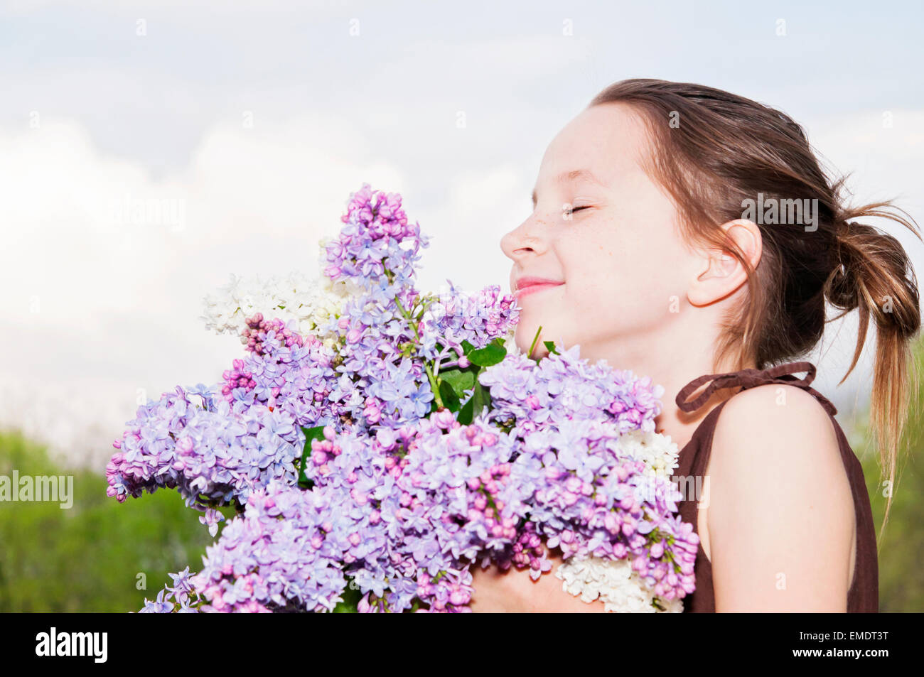 girl smelling lilac flowers - Stock Image