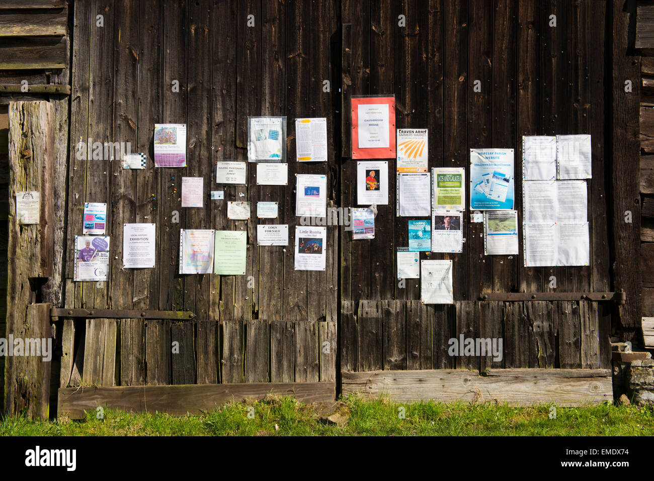 The village noticeboard displayed on the side of an old barn in Hopesay, Shropshire. - Stock Image