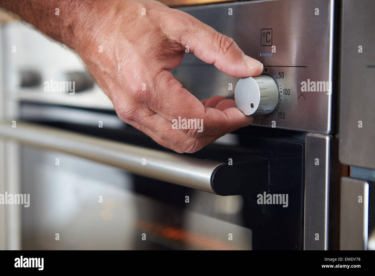 Close Up Of Hand Setting Temperature Control On Oven - Stock Image