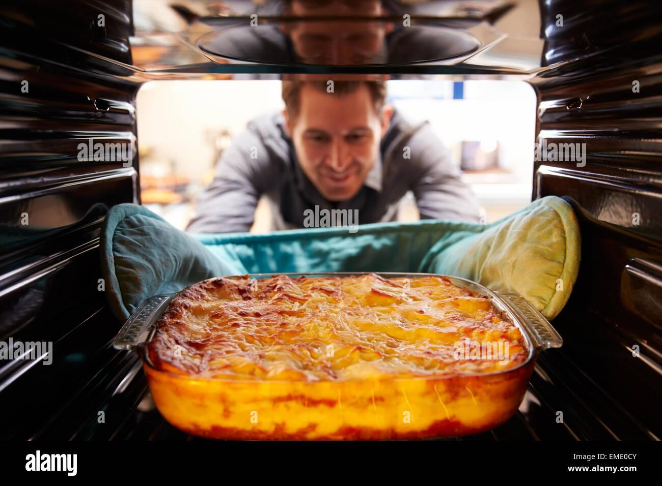 Man Taking Cooked Dish Of Lasagne Out Of The Oven - Stock Image