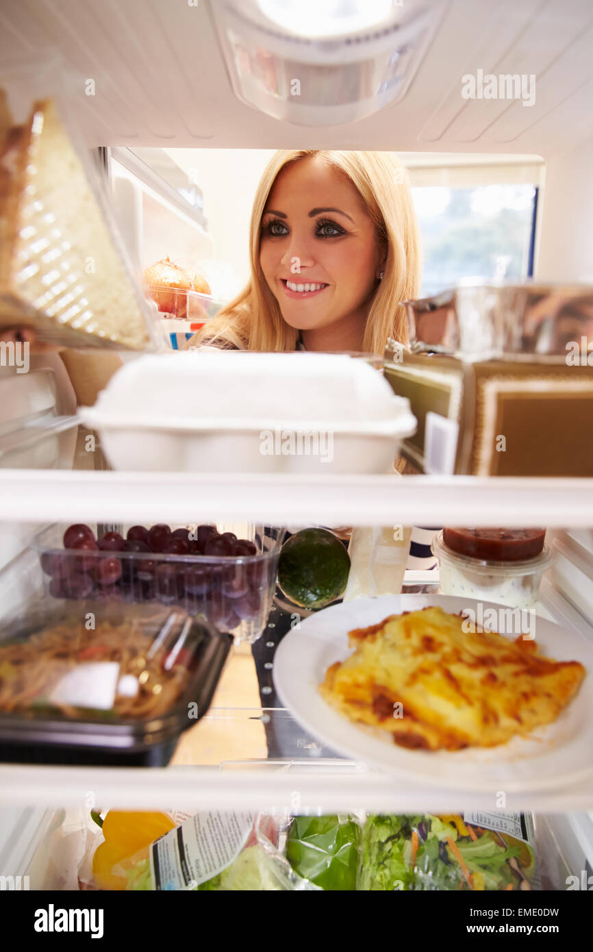 Woman Looking Inside Fridge Of Food And Choosing Sandwich - Stock Image