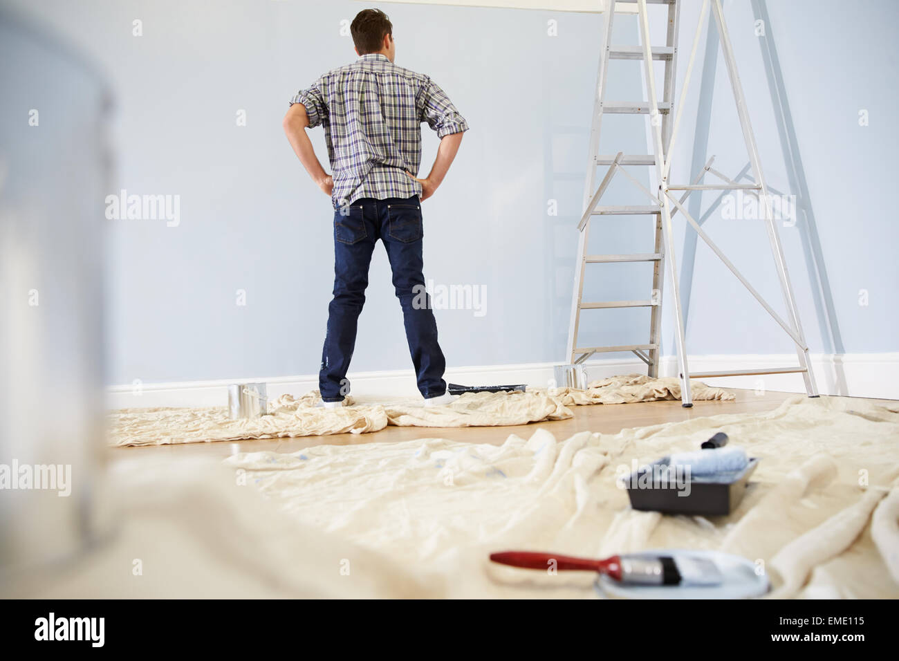 Man Decorating Nursery For New Baby - Stock Image