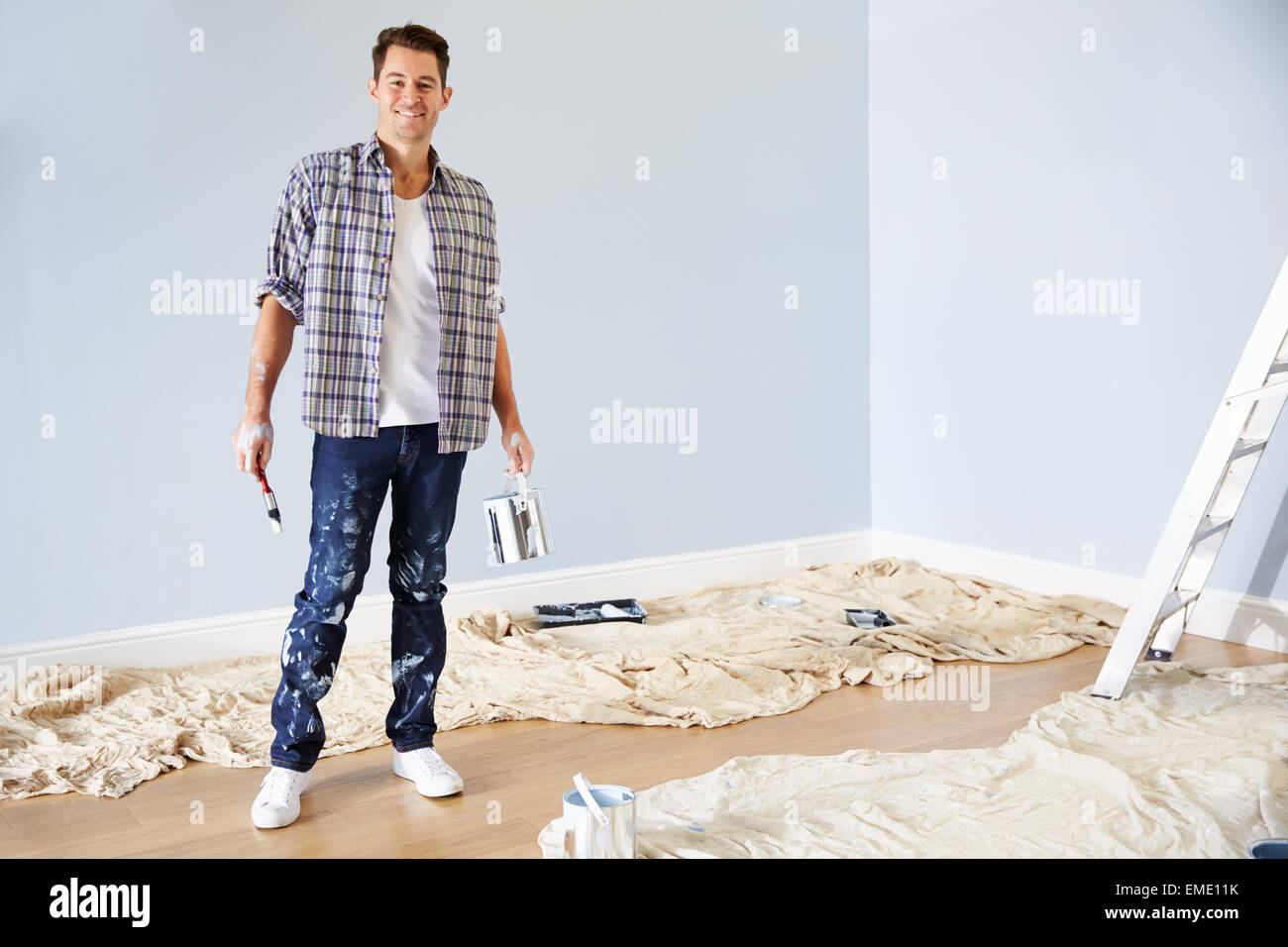 Portrait Of Man Decorating Nursery For New Baby - Stock Image
