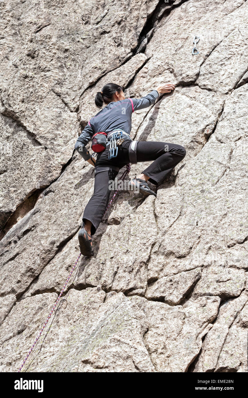 Young woman climbing difficult wall, rock climbing in polish mountains. - Stock Image