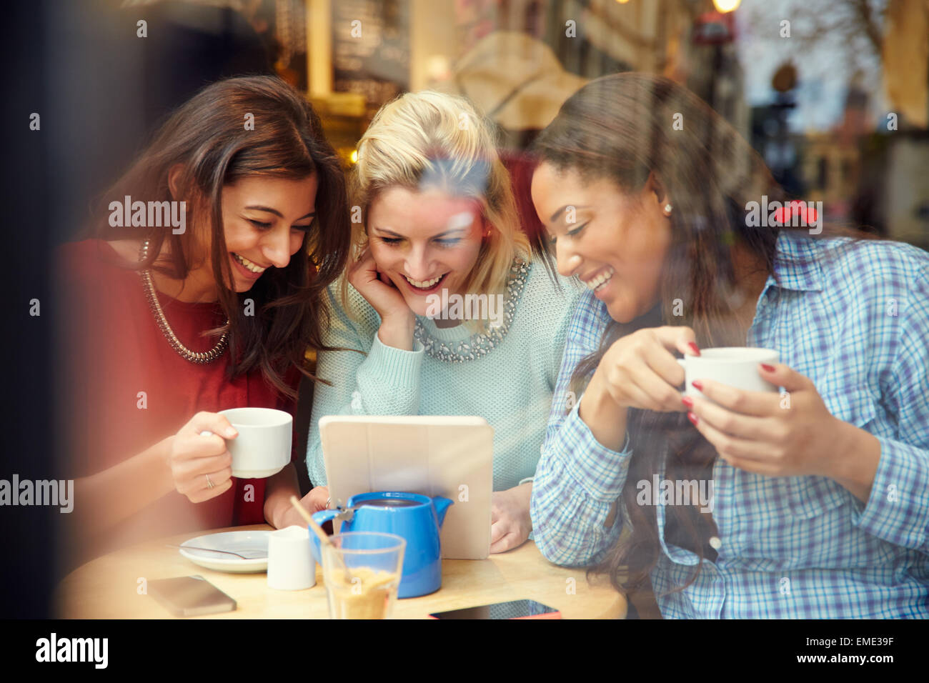 Group Of Female Friends In Caf' Using Digital Devices - Stock Image