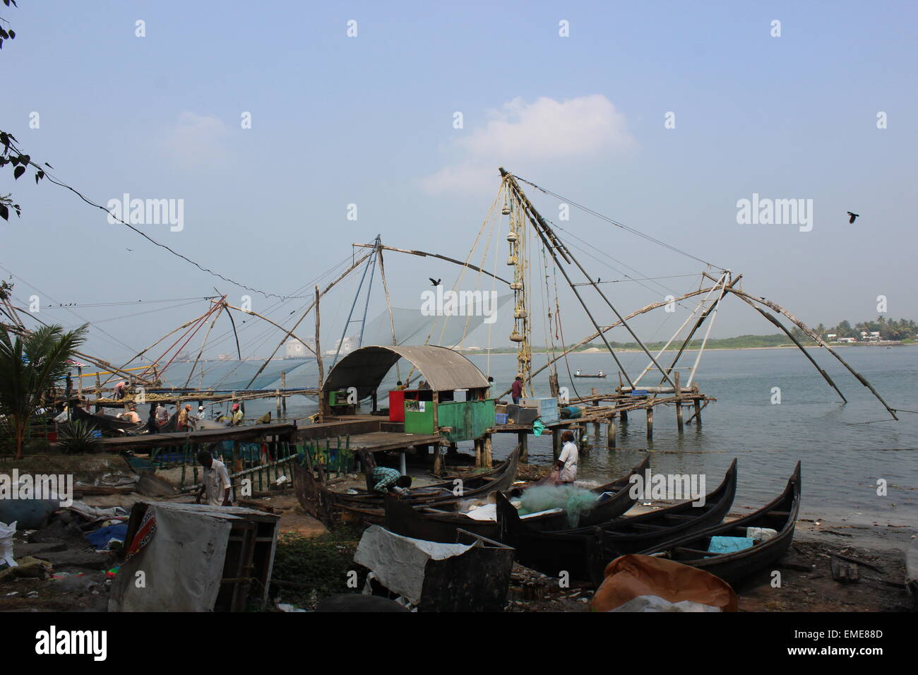 Handling the 'Chinese Fishing Nets' on the waterfront at Fort Cochin. - Stock Image