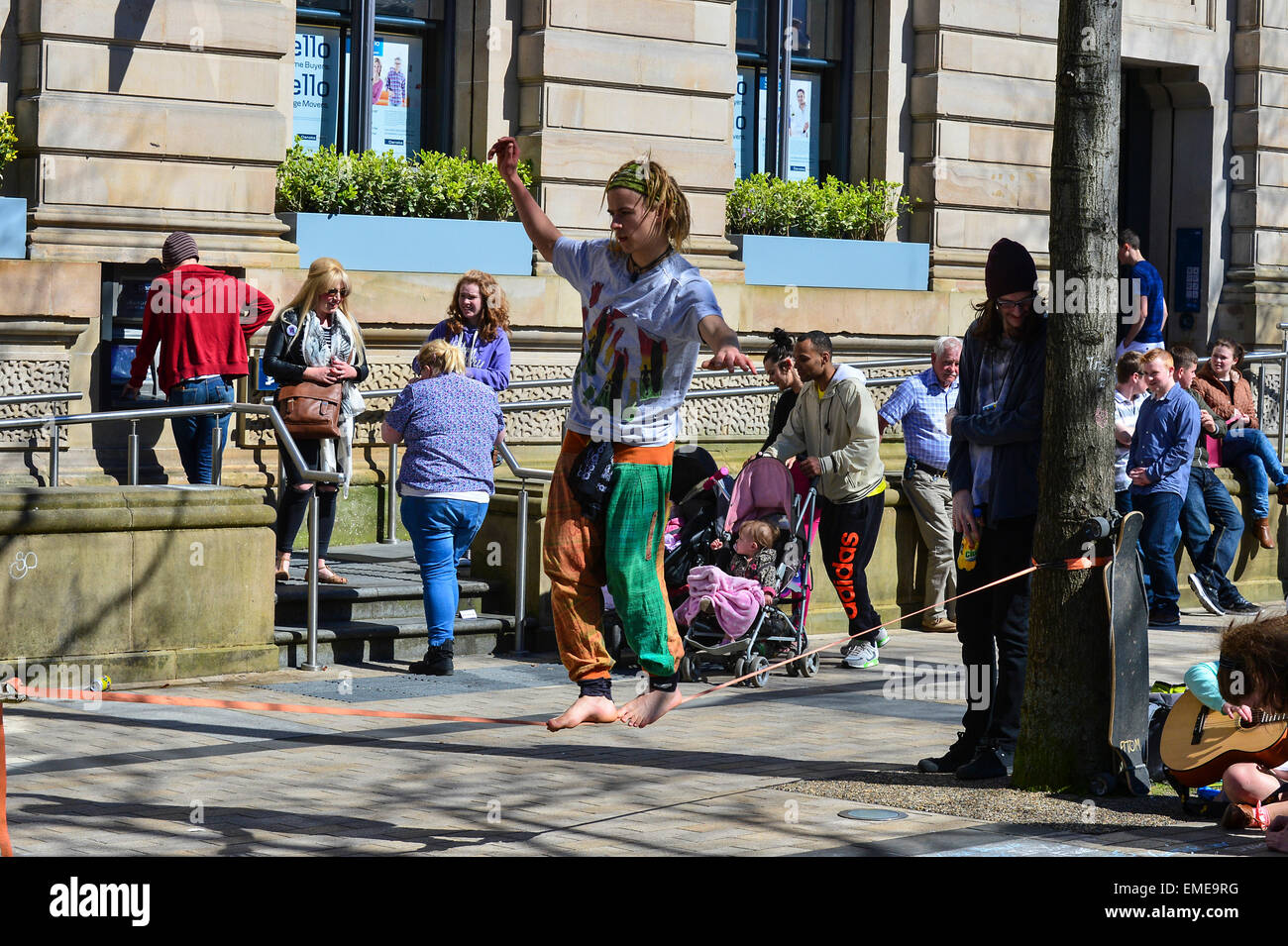 Young street entertainer performs tightrope act in Guildhall Square, Londonderry (Derry), Northern Ireland - Stock Image