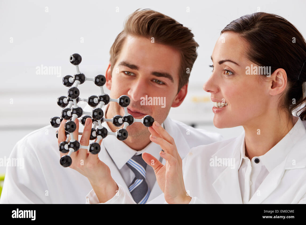 Two Technicians Looking At Molecular Model In Laboratory - Stock Image