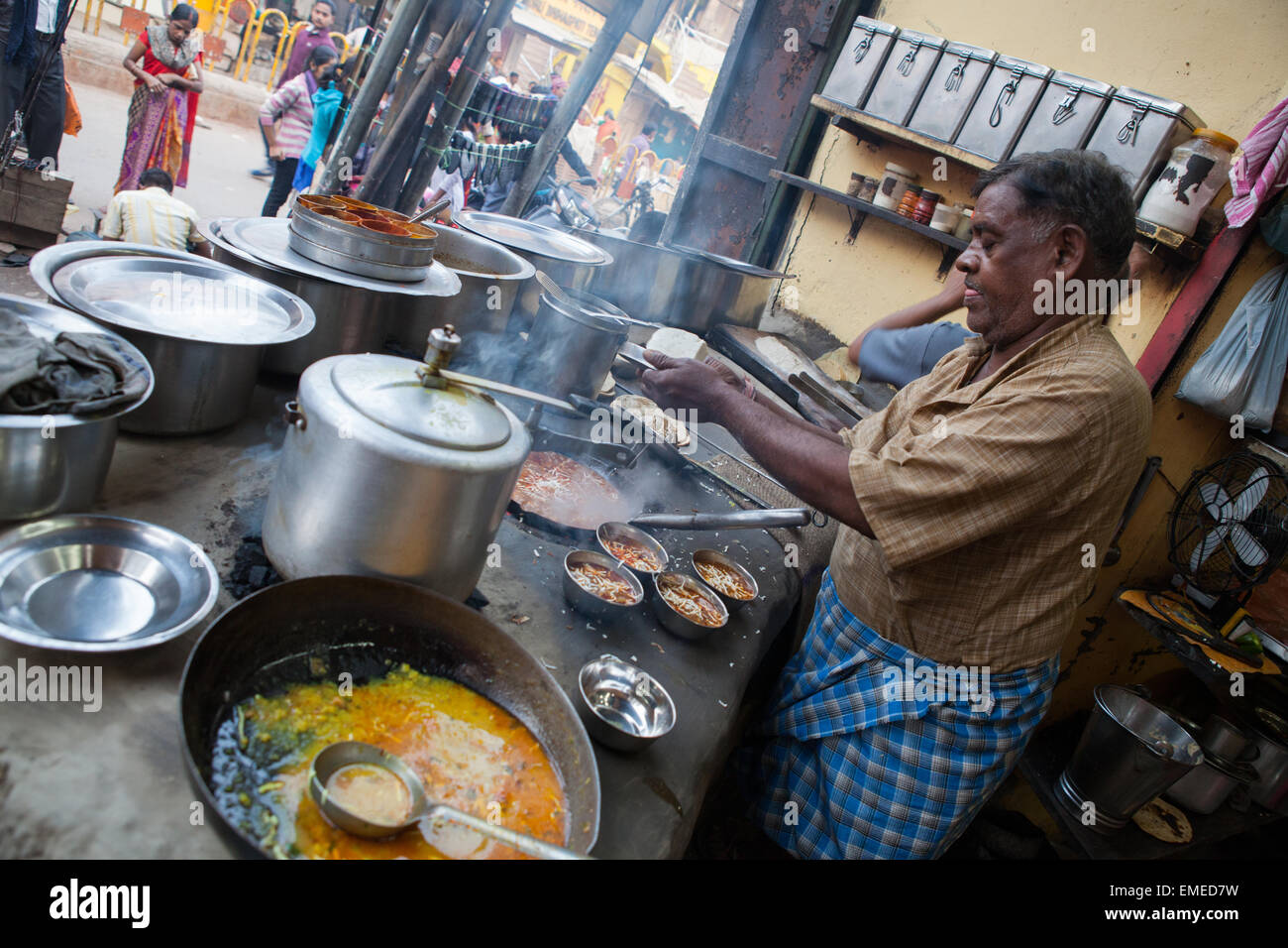 A vendor cooking fried dahl at a food hotel in the old city of Varanasi - Stock Image