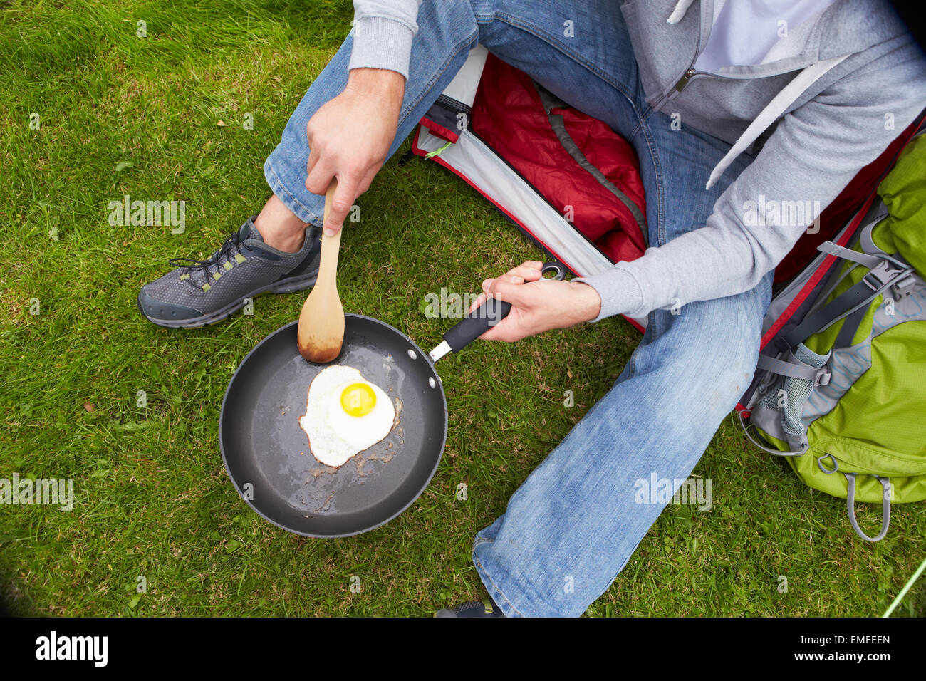 Man On Camping Holiday Frying Egg In Pan Stock Photo