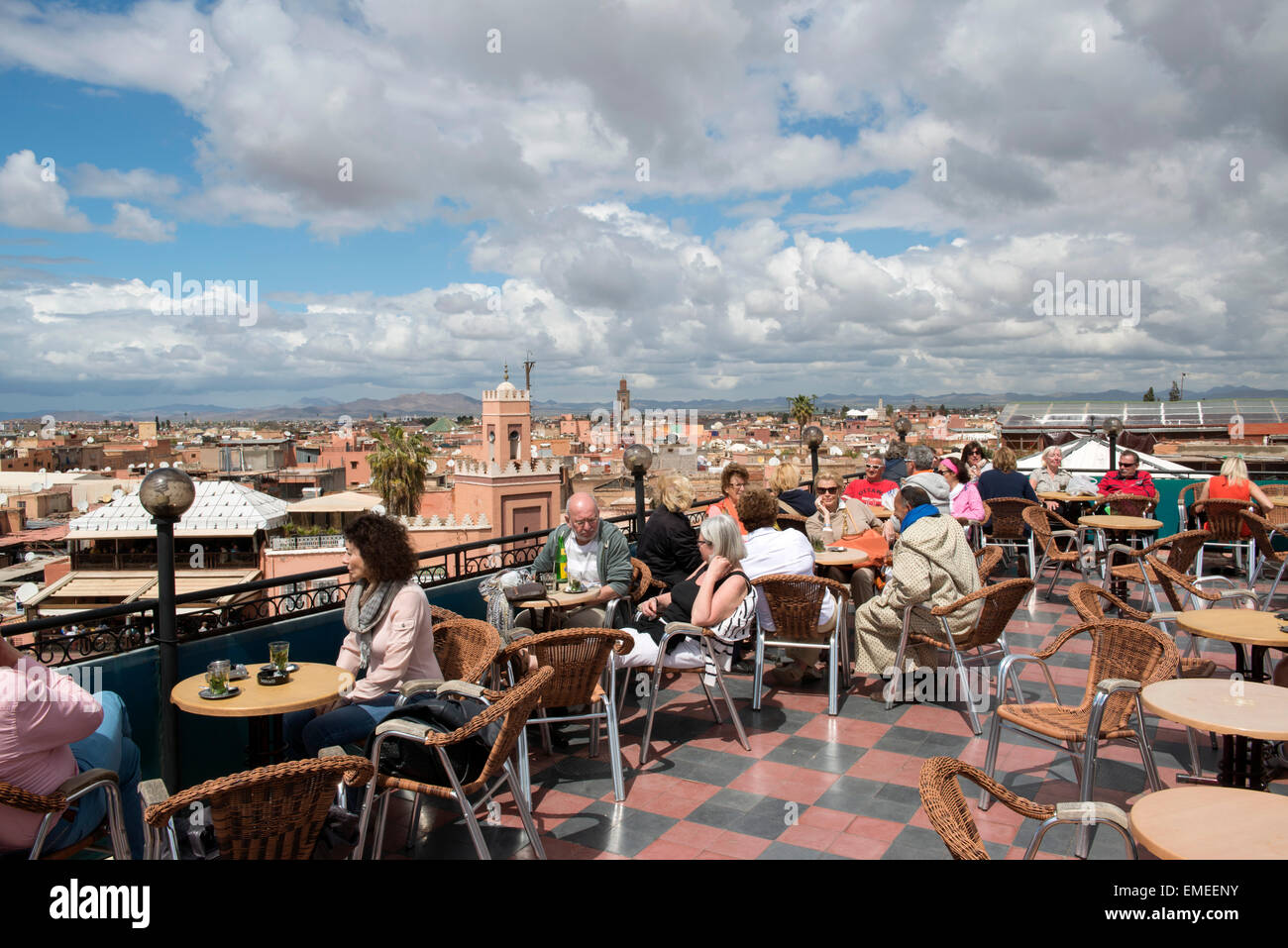 Tourists sit on rooftop terrace at Cafe du France on Jamaa el Fna square and marketplace in Marrakech, Morocco. - Stock Image