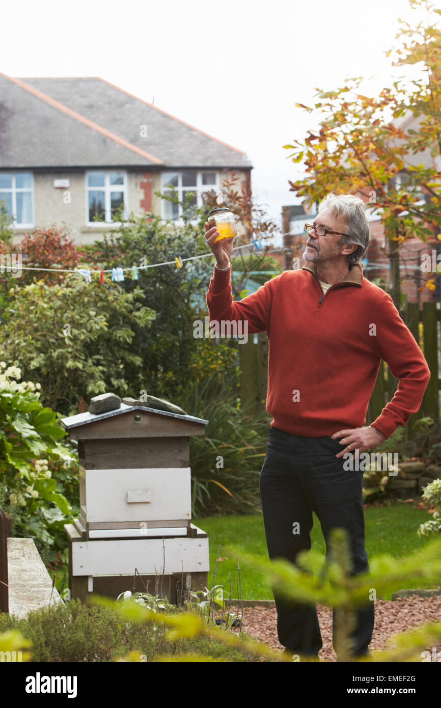 Mature Man Looking At Honey Produced By His Own Bees - Stock Image