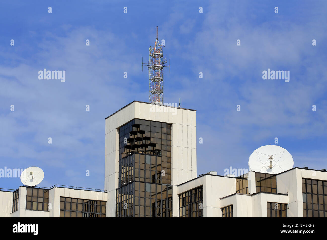 Top of the tech building with glass walls and radio equipment on the roof - Stock Image