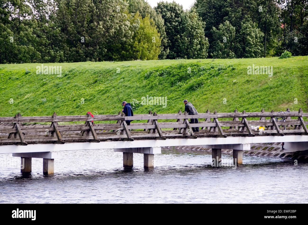 Klaipeda Lithuania men fishing from bridge crossing moat beside old earthen fort rampart defense walls built in - Stock Image