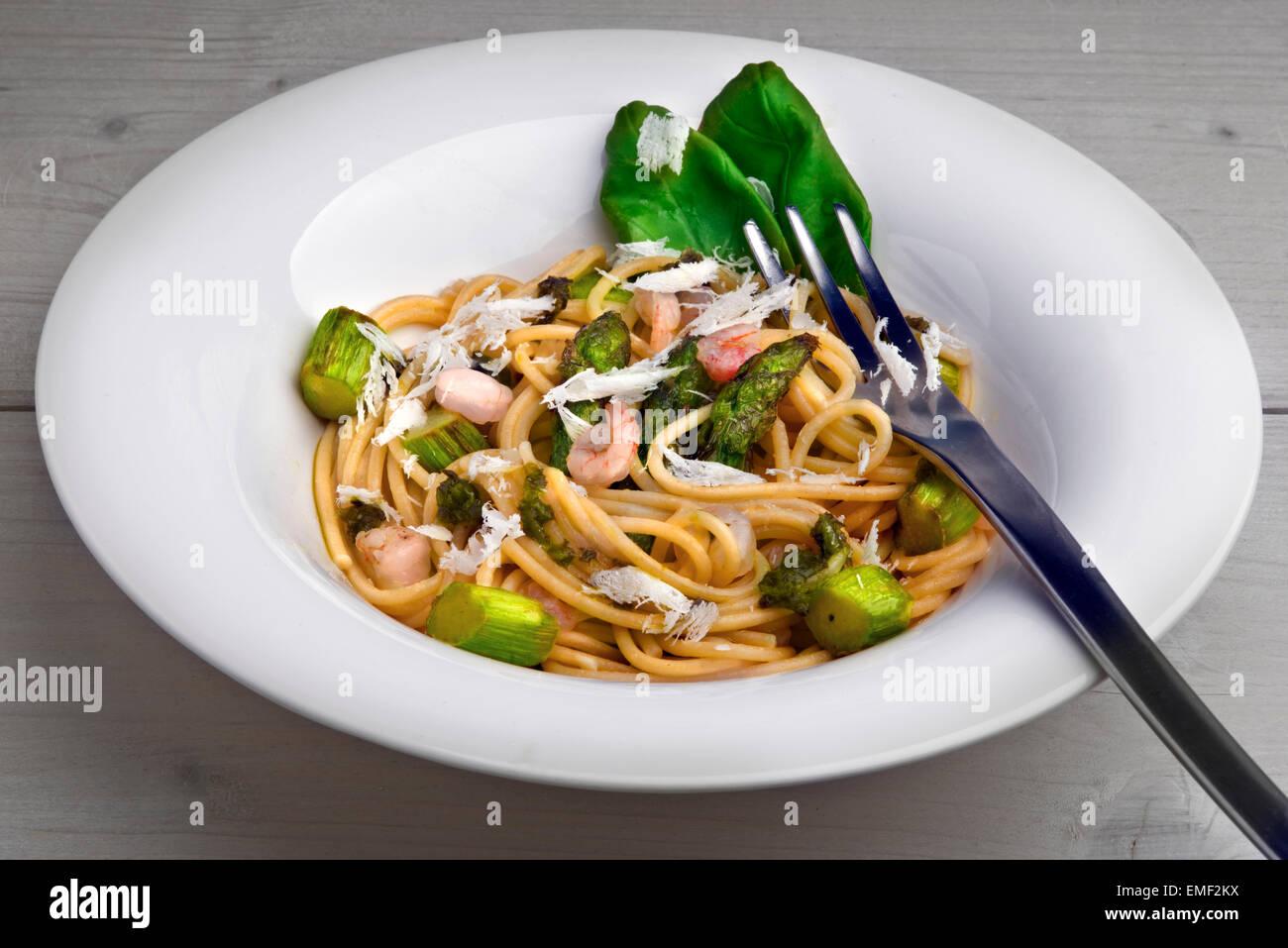 Whole grain pasta with green asparagus, shrimp, wild garlic (buckrams) pesto, parmesan shavings and basil leaves. - Stock Image