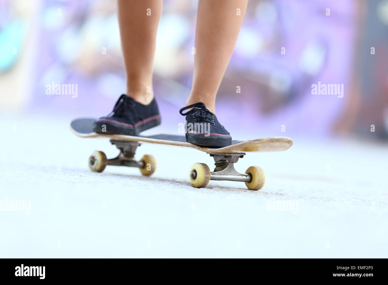 Teenager skater girl legs on a skate board with a graffiti wall in the background - Stock Image