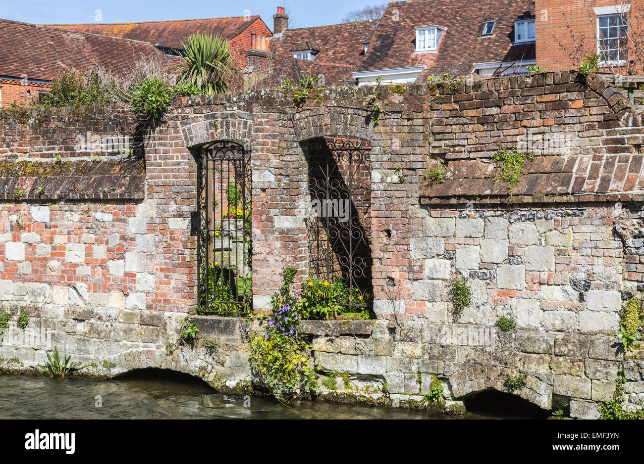 Wrought iron gates in gateways in an old brick wall fronting the River Itchen, Winchester, Hampshire, UK - Stock Image