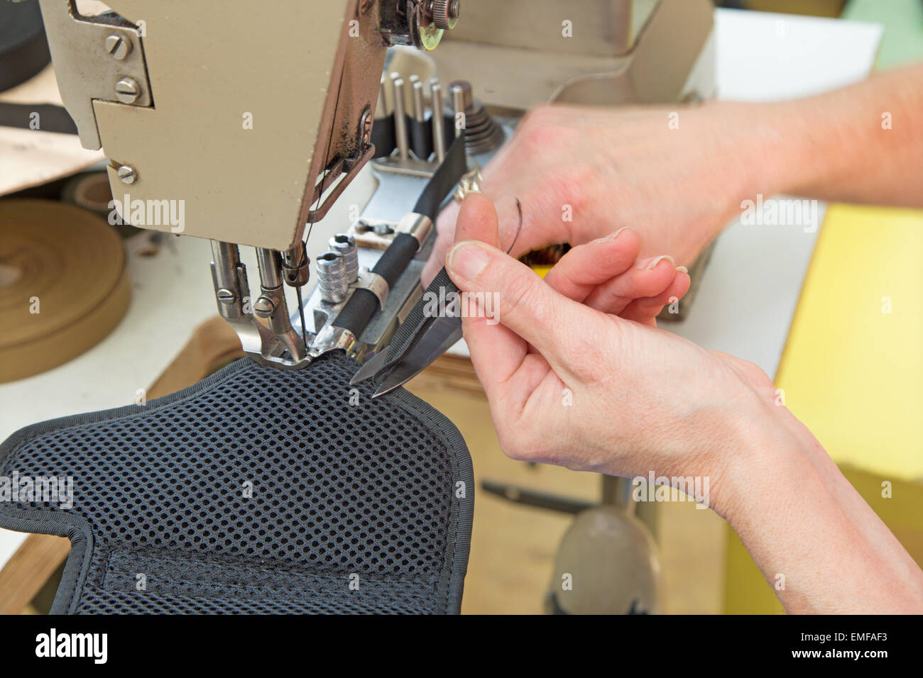 hands of the woman at the needlework of the colt case - Stock Image