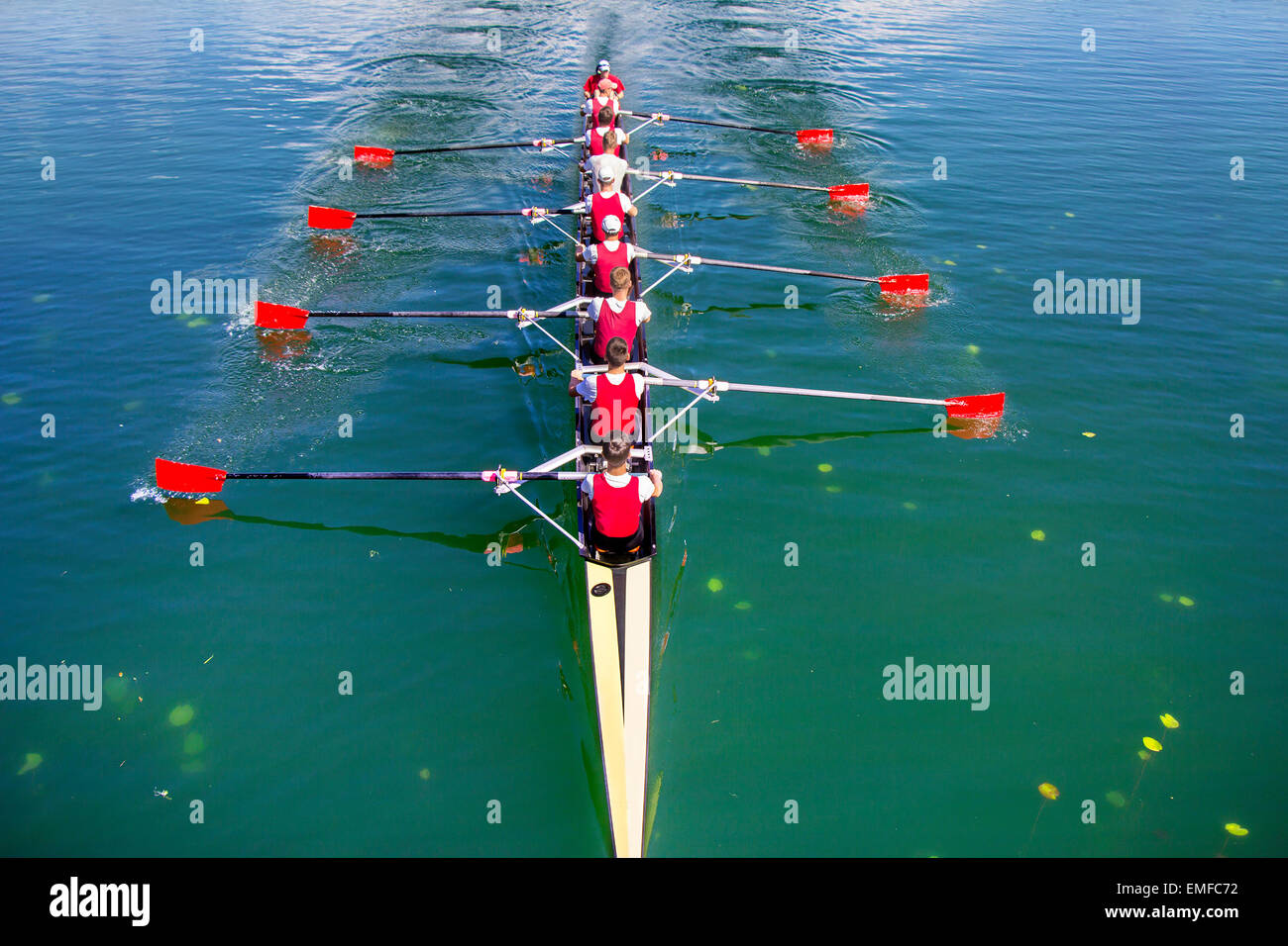 Boat coxed eight Rowers rowing on the blue lake - Stock Image