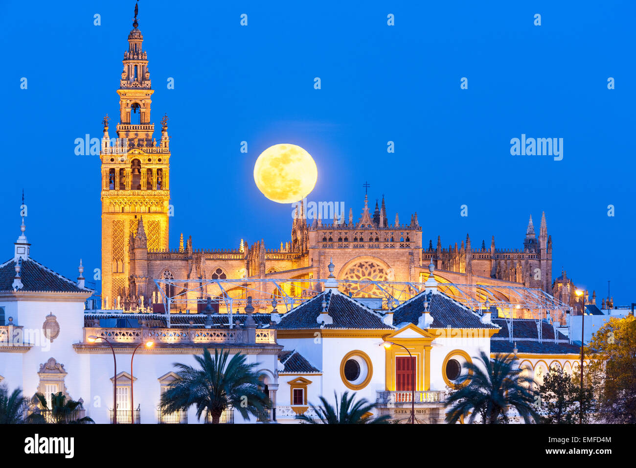 Seville Spain Seville Skyline with full moon rising behind La Giralda tower, Seville Cathedral de Sevilla, and Plaza - Stock Image