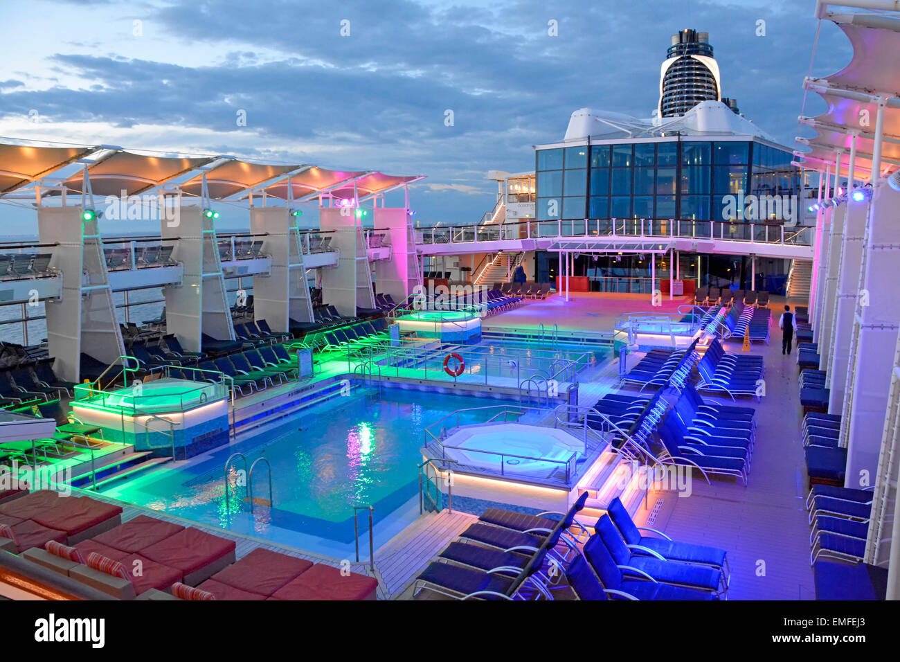 Flood lighting on cruise ship pool deck at end of day with passengers below decks for evening meal (for day view - Stock Image