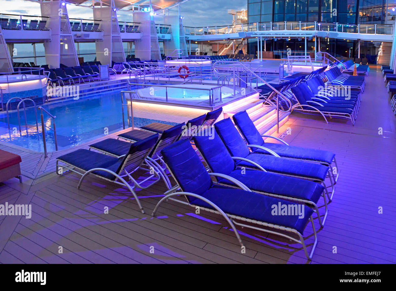 Blue night lighting on cruise ship pool deck at end of day with passengers below decks for evening meal ocean liner - Stock Image