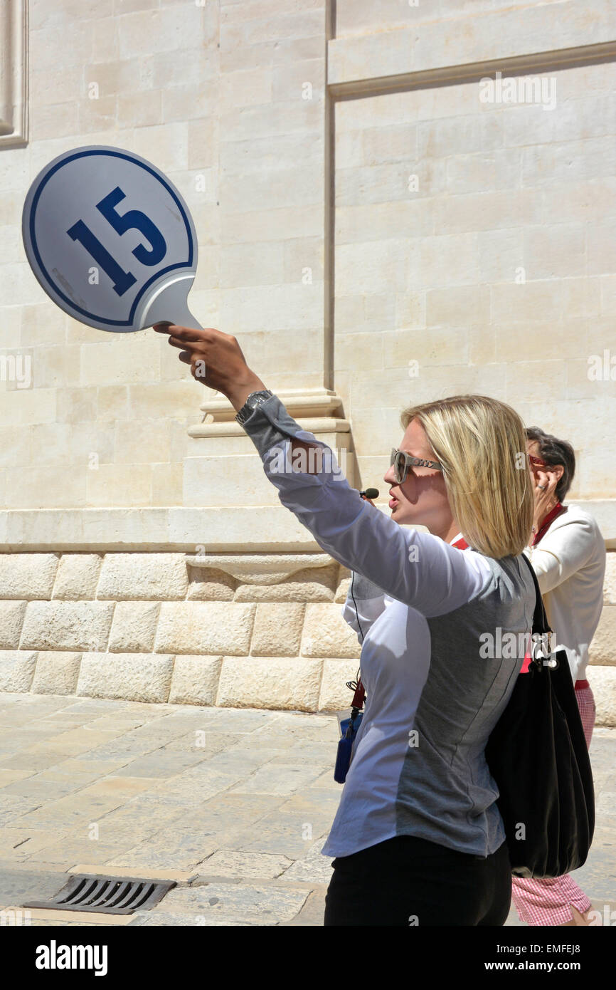 Cruise tour guide pointing her number board at points of interest during her speaking tour (cruise ship name digitally - Stock Image