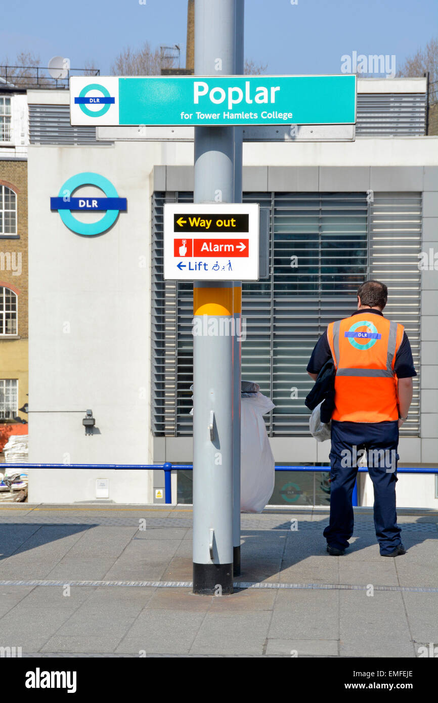 Docklands Light Railway employee standing on Poplar station platform with DLR depot and logo beyond - Stock Image