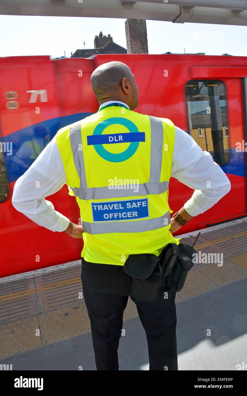 Docklands Light Railway 'Travel Safe Officer' standing on station platform as train arrives - Stock Image