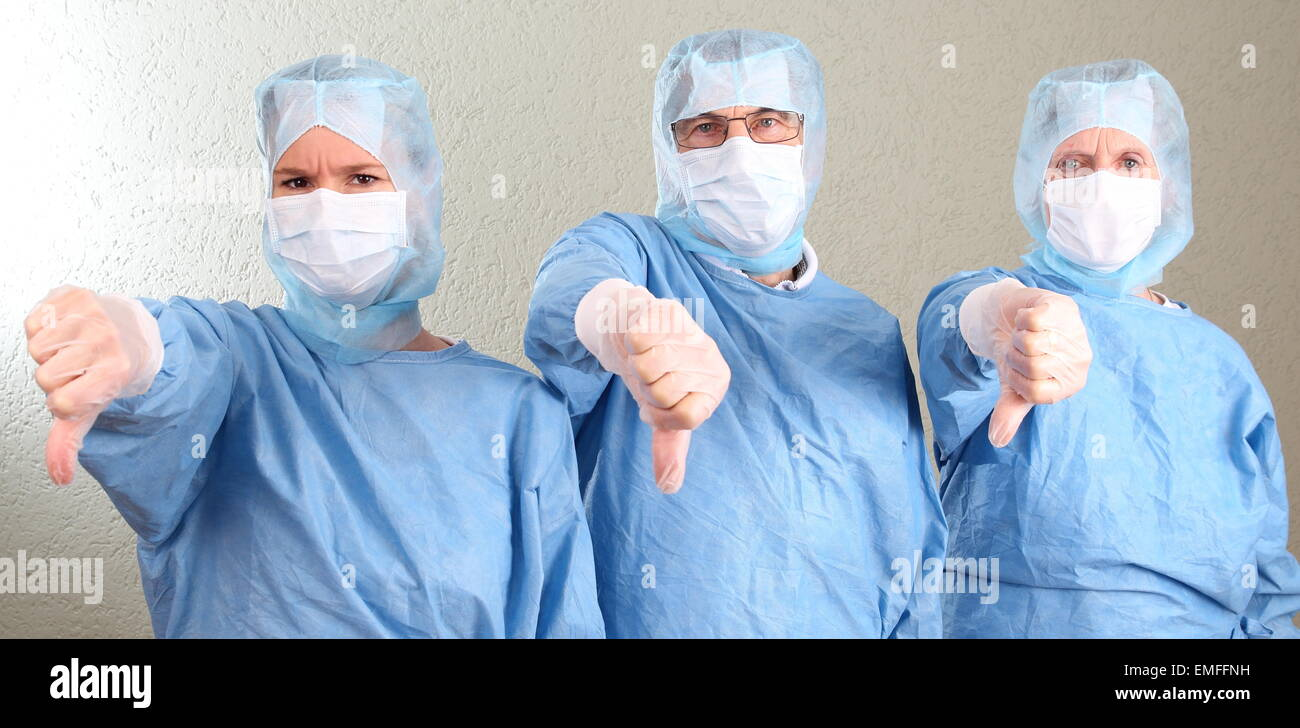 Three Doctors with thumbs down - Stock Image