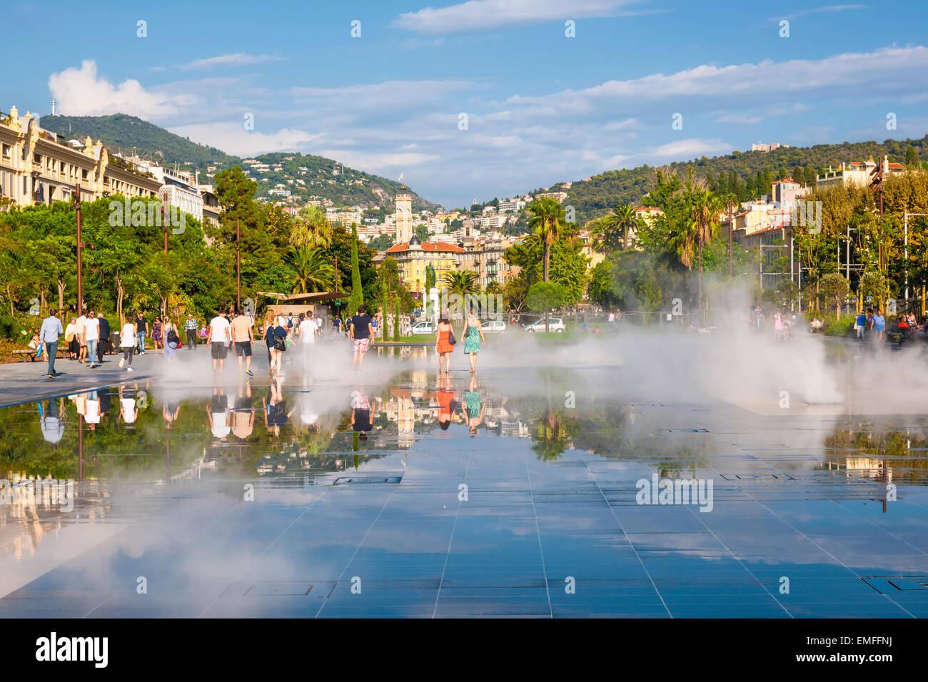 NICE, FRANCE - OCTOBER 2, 2014: People walking through soaking fountain on Promenade du Paillon reflecting the city Stock Photo