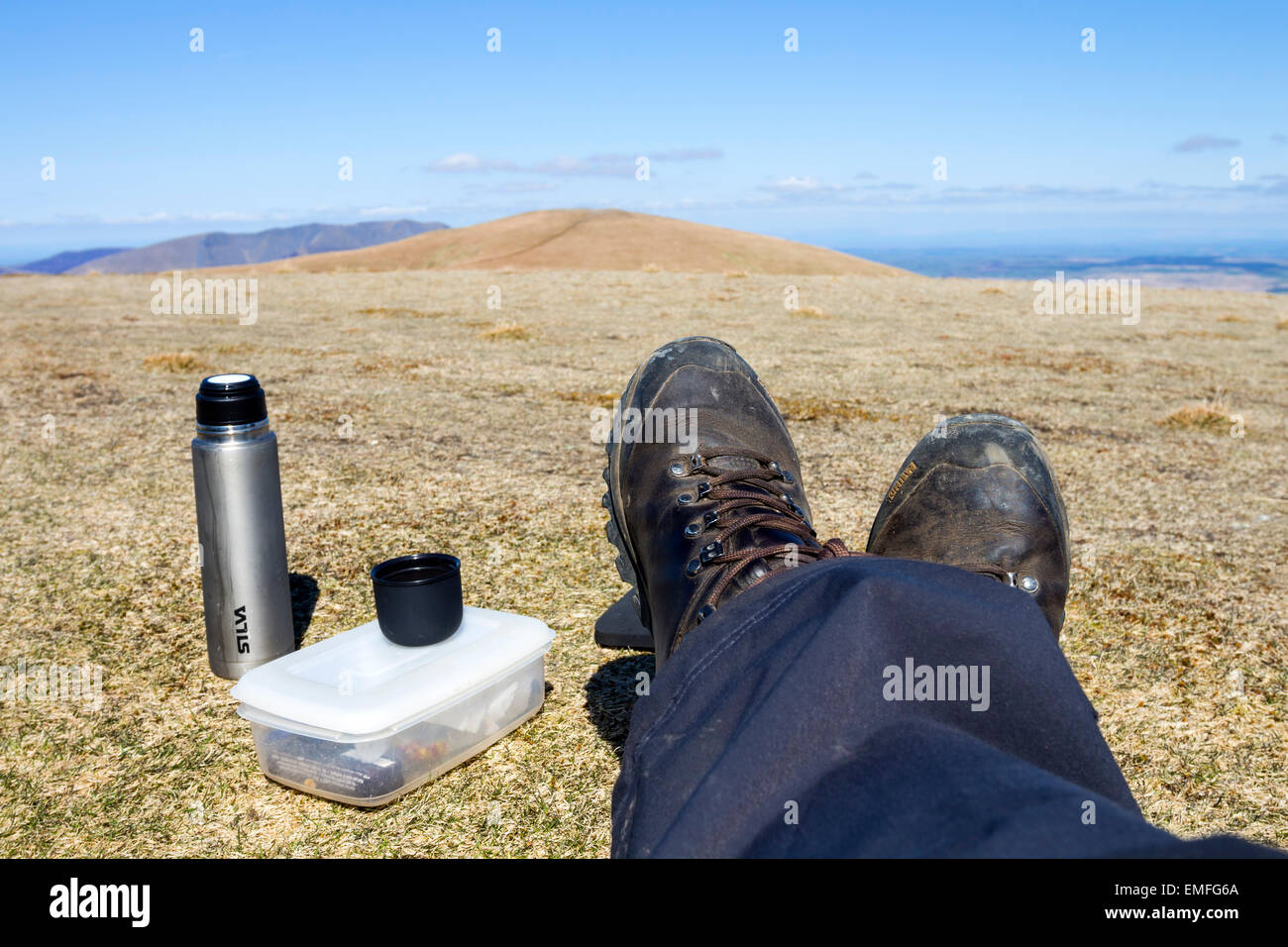 Walker With Feet up and a Packed Lunch on Stybarrow Dodd with the Rounded Summit of Watson's Dodd in Background - Stock Image