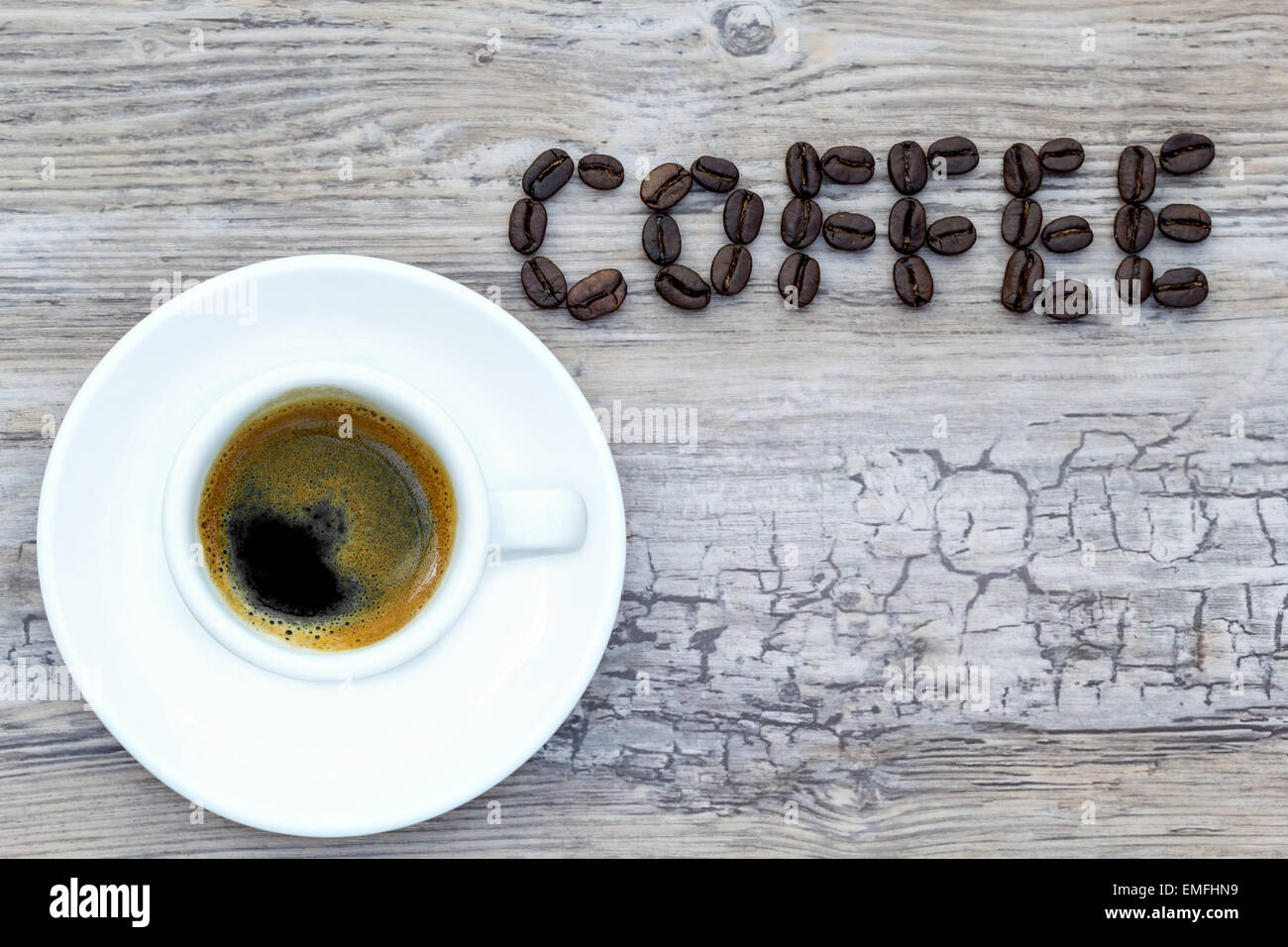 Filled espresso cup with text coffee out of beans from above Stock Photo