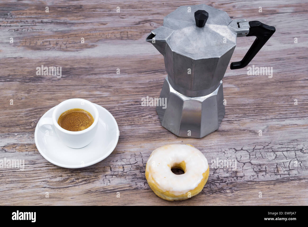 Espresso with a glazed donut on a wooden table from above with copy space - Stock Image