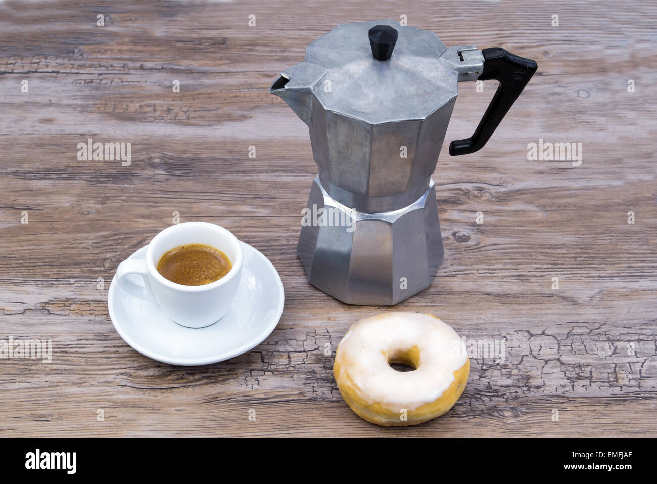 Espresso with espresso maker and a glazed donut on a wooden table from slightly above - Stock Image
