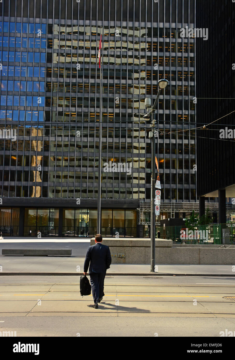 Lone business man walk towards an office building - Stock Image