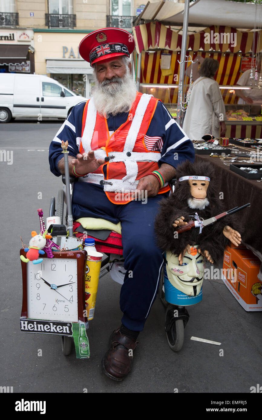 Portrait of a man with a physical disability sitting in a wheelchair asking for donations in Paris, France - Stock Image