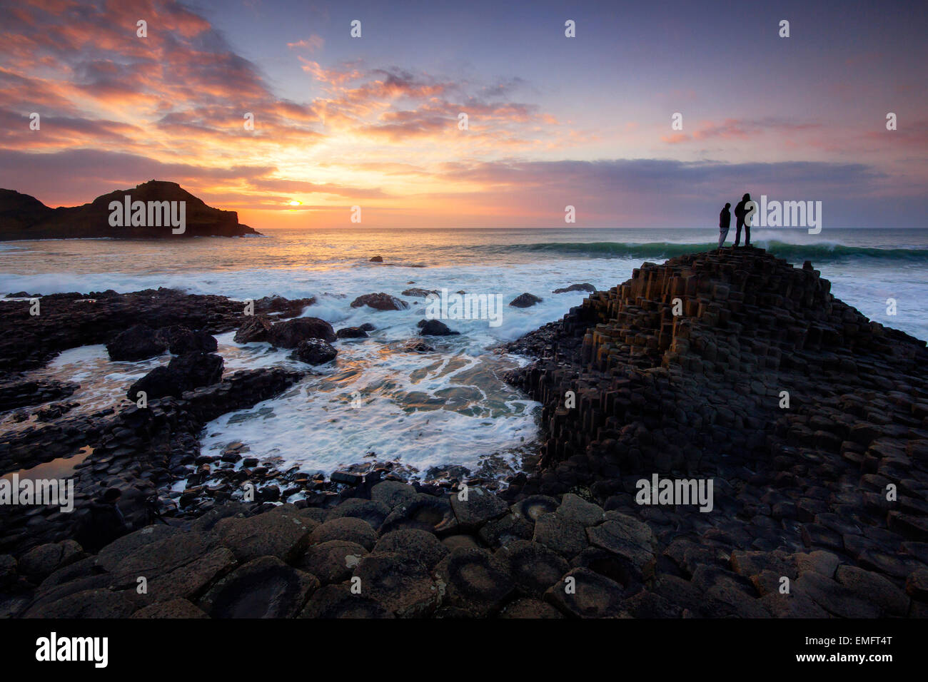 Tourists watching a sunset at the Giant's Causeway - Stock Image