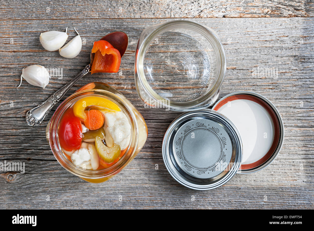 Home preserving mixed vegetables by pickling in glass canning jars - Stock Image