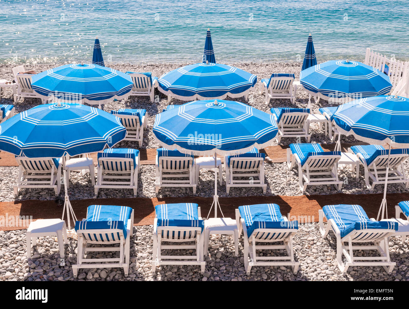 Blue umbrellas and chairs on pebble beach in Nice, France. - Stock Image