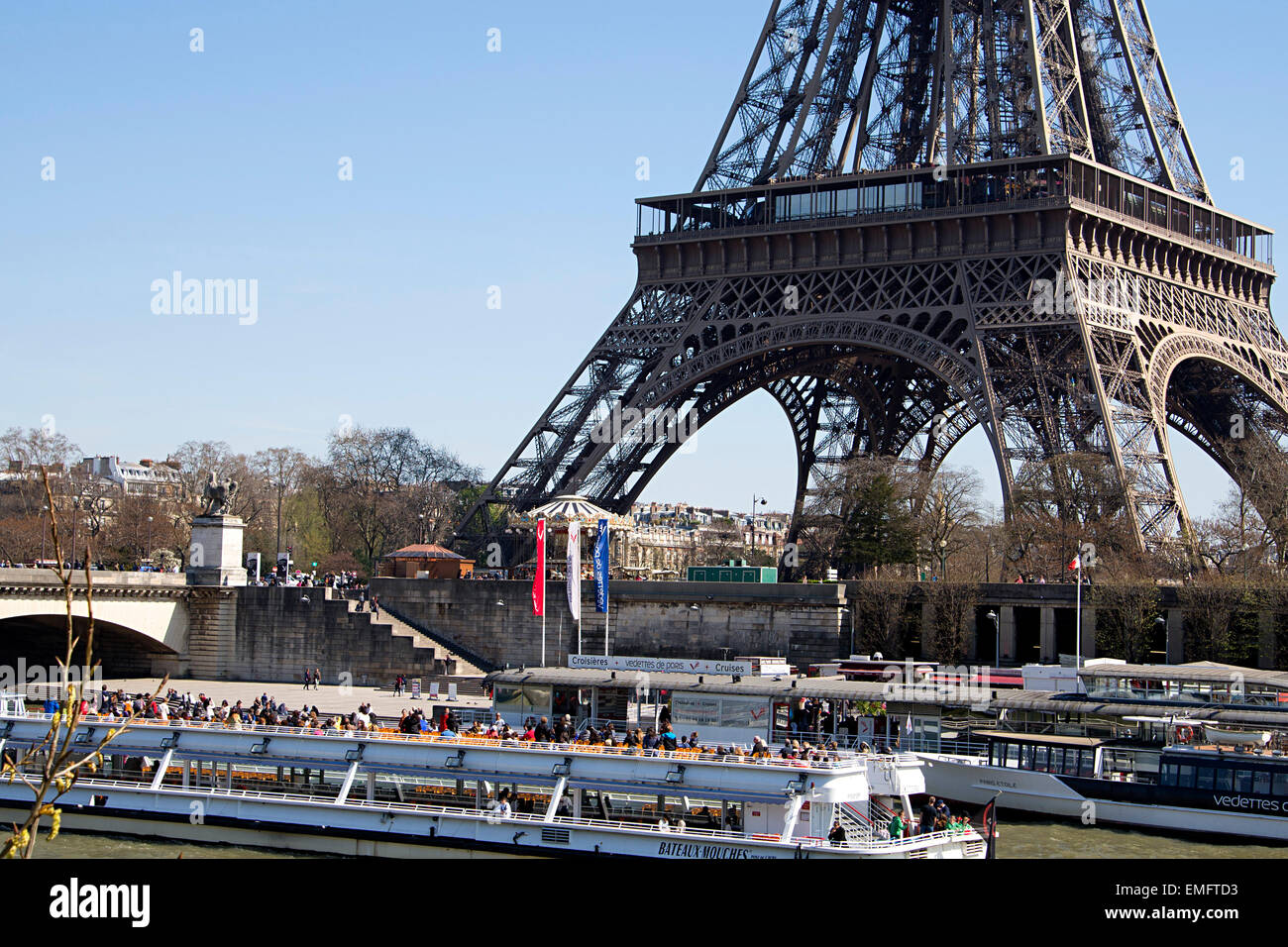 Paris Eiffel Tower cruisers, motor launches, cruises, carousel attractions for visitors. - Stock Image
