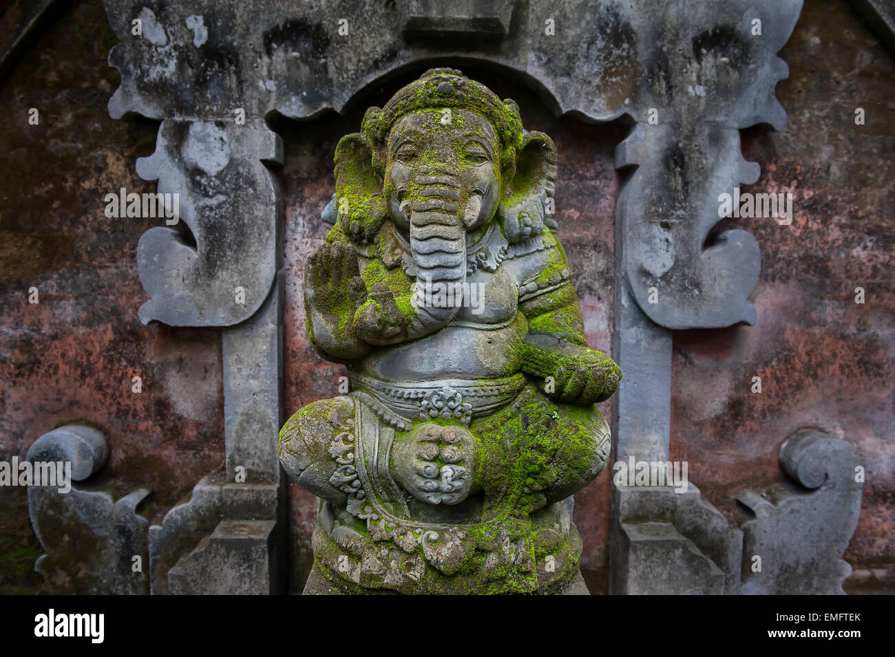 Sculpture of Ganesha covered with mold and moss. Traditional Hindu culture. Divine spirituality and total humidity - Stock Image