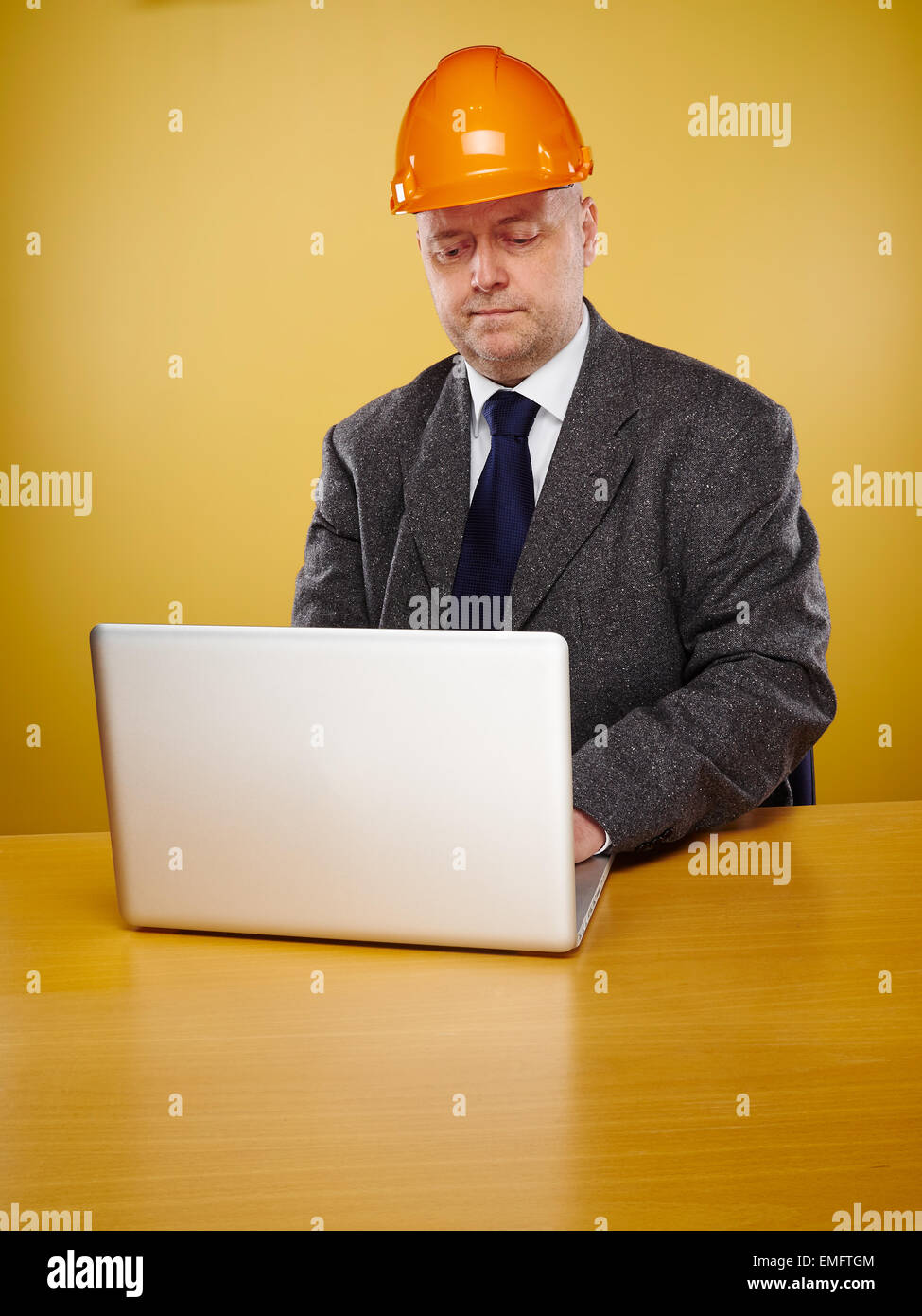Working male engineer in office, he wearing a white shirt and tie and coat, head he wears a orange hard hat - Stock Image