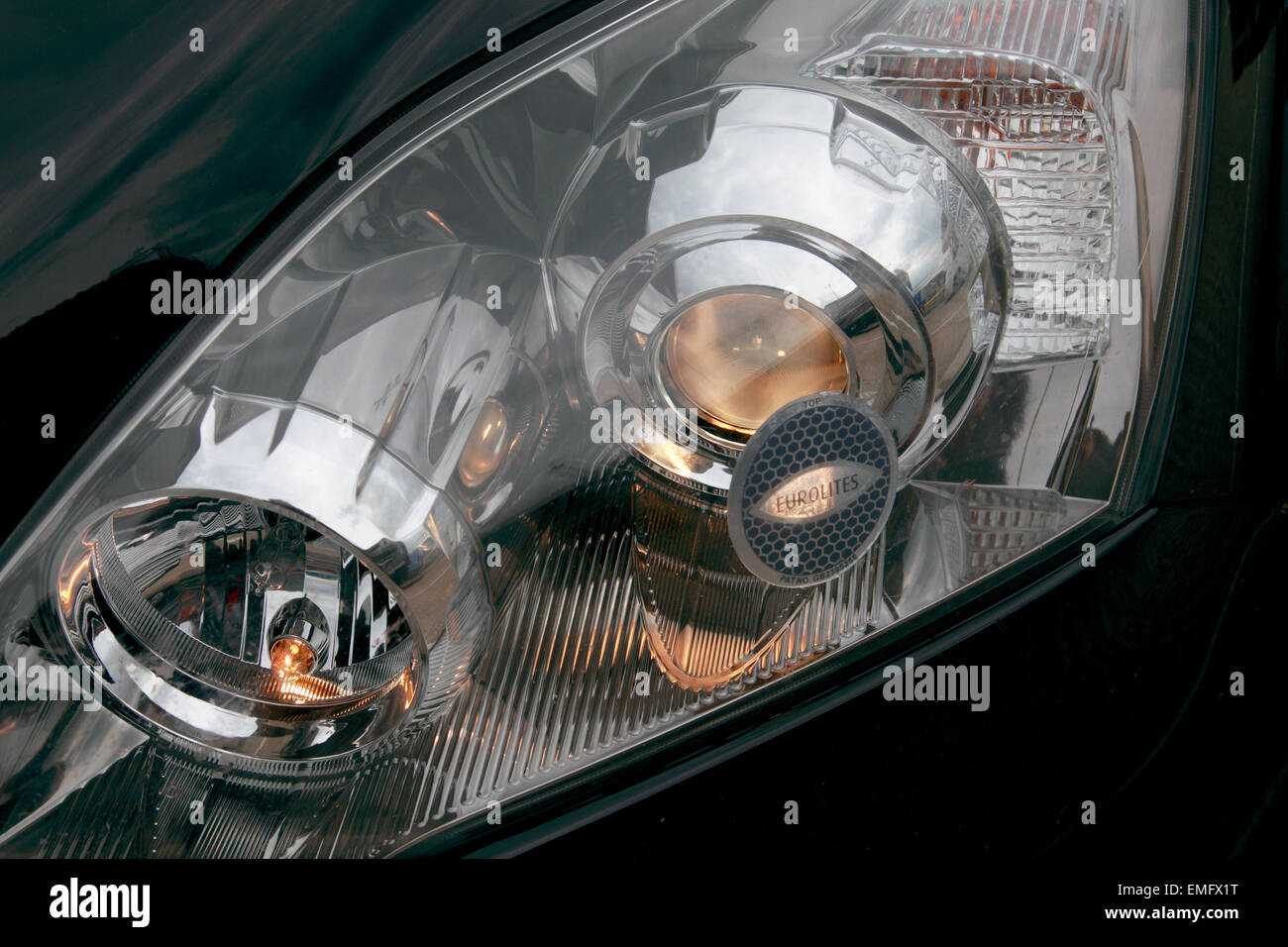 Headlamp beam adaptors fitted on to the headlights of a car - Stock Image