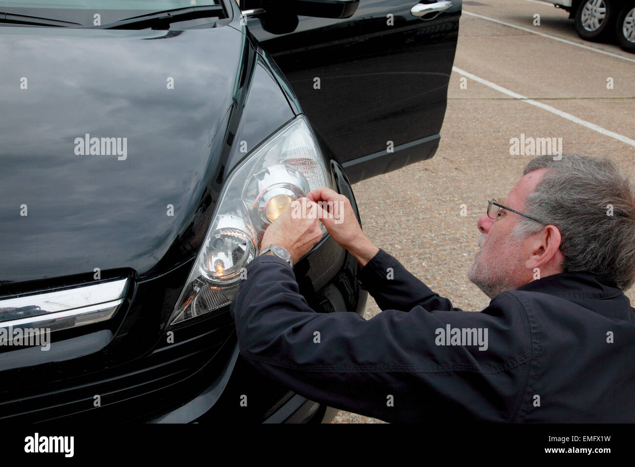 A man fitting headlamp beam adaptors on to the headlights of a car - Stock Image