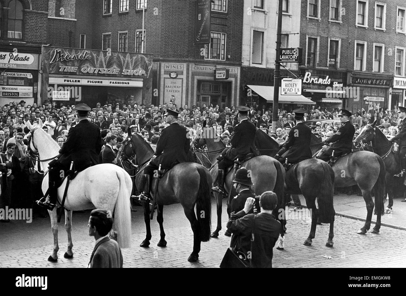 Mounted police seen here trying to control a large crowd gathered in Ridley Road E8 after former fascist leader - Stock Image