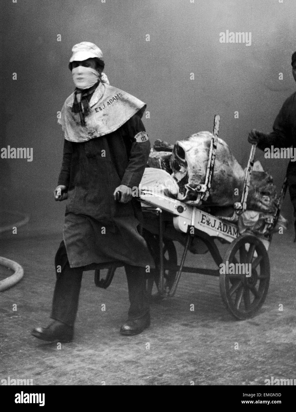 Meat porters carried on with their work with mouths covered against the smoke as the fire continue at Smithfield - Stock Image